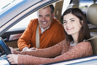image of dad teaching daughter how to drive